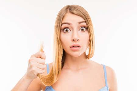 split ends: Young shocked woman showing her damaged split ends