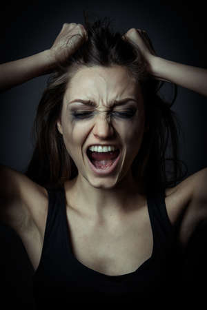 Close up portrait of a scared screaming girl, hands on the forehead