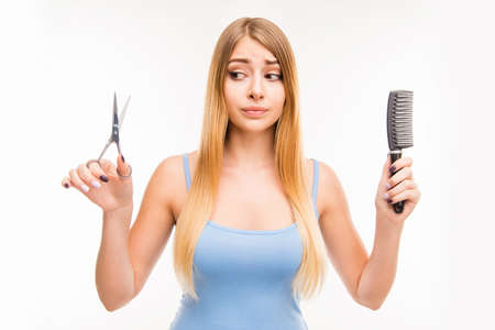 convenience: Girl chooses scissors or comb, beauty or convenience, long hair or short