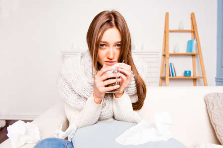 grippe: Sick woman with rheum holding a cup of tea