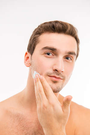 cheek: A young handsome man with shaving cream on his cheek
