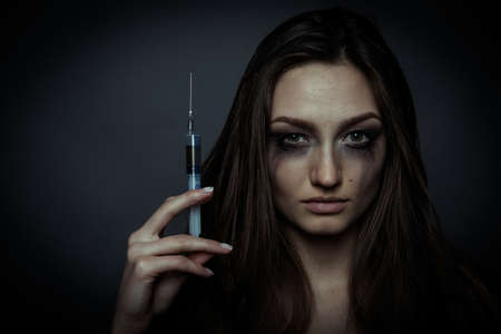 drug use: Young sad woman holding a syringe to drug use Stock Photo