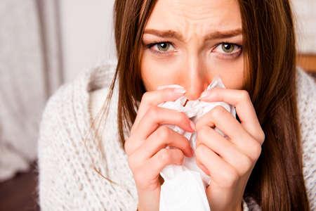 Chiuda sul ritratto della donna malata con febbre che starnutisce nel tessuto