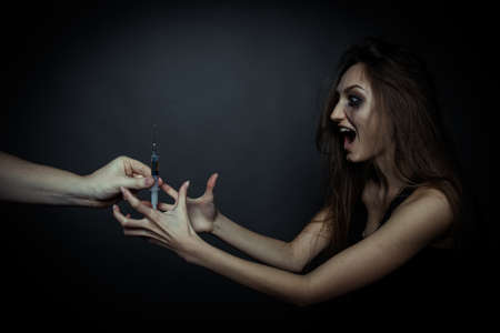 Young sad woman taking a syringe to drug use and screaming Stock Photo