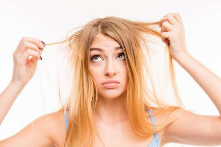 pelo: Muchacha triste que mira su cabello da�ado