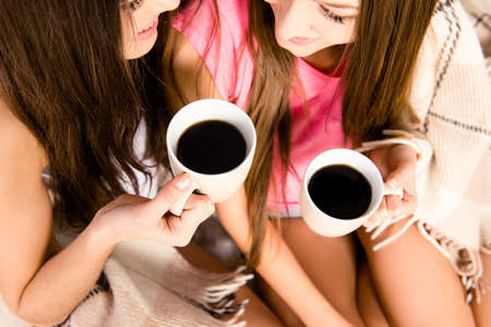 lesbo: Two girls with cups of coffee in hands,  close up photo