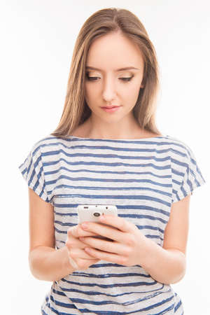 minded: Minded young woman typing sms on mobile phone