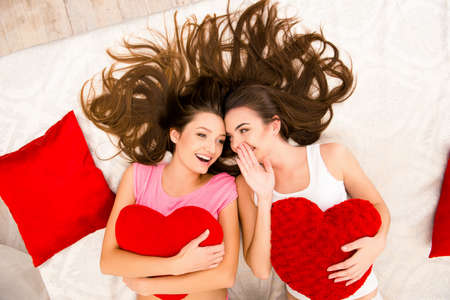 sex on bed: Cheerful beautiful girls in pajamas gossiping and lying on the bed holding pillows