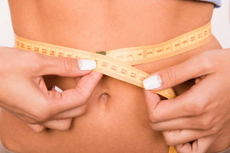 enteric: Close up photo of girls waist with a measuring tape