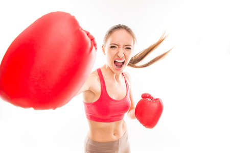 striking: Beautiful angry sportswoman in red boxing gloves and striking