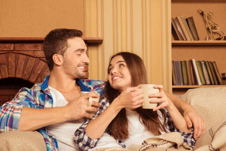 casados: Pareja feliz en el amor con la tela escocesa y las tazas se relaja en el sofá