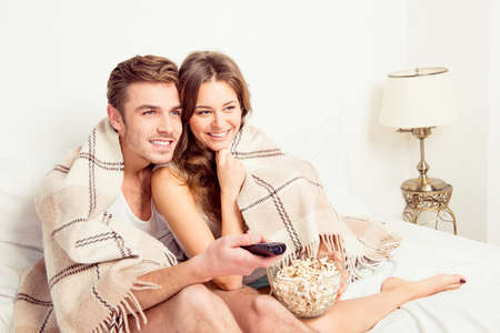 comedy: Young beautiful couple in love at home under plaid with popcorn