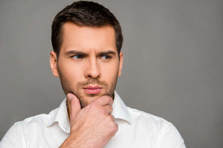 pensiveness: A confident man in a white shirt standing on the gray background Stock Photo