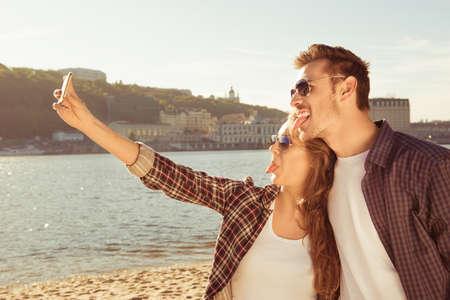 haciendo el amor: pareja en la playa hace autofoto y sonriente