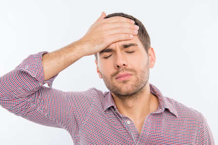 spite: Handsome young man touching his head with one hand feeling strong headache