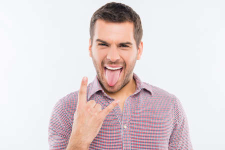 sexy brunette: Cheerful young man gesturing with two fingers and showing tongue