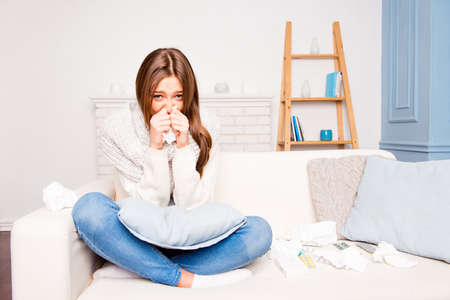 bad girl: Sick  girl with fever sneezing in tissue sitting on sofa, close up photo