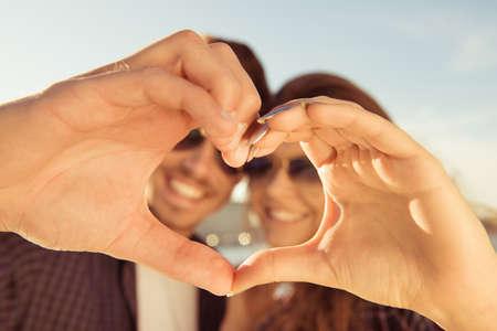happiness: feliz pareja romántica en el amor haciendo un gesto con los dedos un corazón