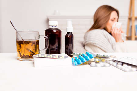 Chora kobieta, filiżanka herbaty, pastylki i mieszaniny, zamknąć zdjęcie