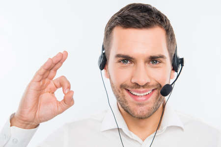 Smiling agent of call centre gesturing OK