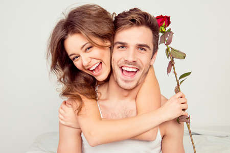 amantes en la cama: Alegre joven pareja en el amor que abraza en el dormitorio con la rosa