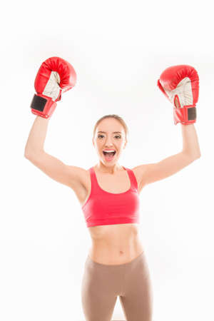 triumphing: Positive sporty girl in boxing gloves triumphing