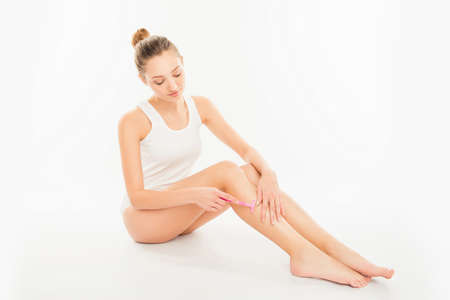 depilate: Pretty young woman shaving her leg on white background Stock Photo