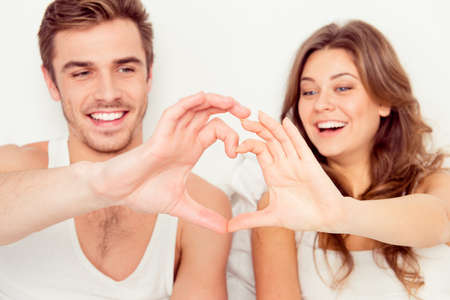 sex symbol: Happy romantic couple in love gesturing a heart with fingers