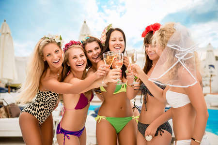 hen party: Happy sexy girl clinking  glasses at brides hen party  by the pool Stock Photo
