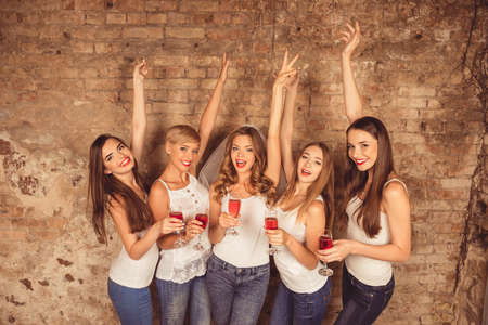 Cheerful bride and happy bridesmaids celebrating with red champagne