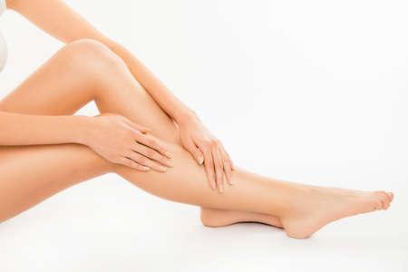 beautiful smile: Closeup photo of cute pretty young woman touching her legs Stock Photo