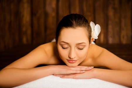 sauna nackt: Attractive young girl lying with closed eyes in sauna