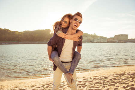 carrying girlfriend: Happy young man piggybacking his girlfriend near the sea.