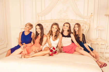 bridesmaids: Bridesmaids sitting on a luxury bed and smiling