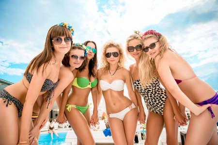 traje de bano: muchachas bonitas con gafas y trajes de ba�o relajante en la piscina en el complejo
