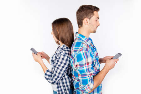 internet love: Two lovers standing back to back and typing message on phones