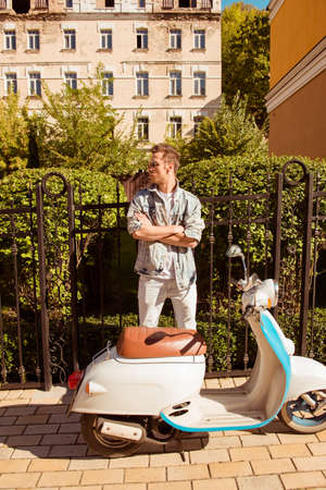moped: Trendy young man standing with crossed hands near moped Stock Photo