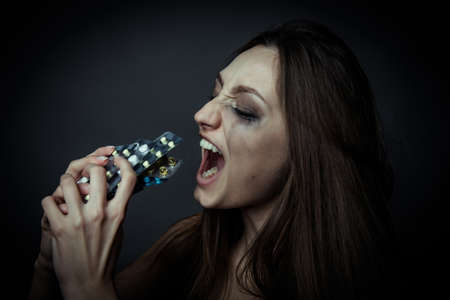 intoxicated: Young depressed woman ussing pills or drugs Stock Photo