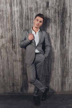 handome: Handome man in suit on the grey background with hand in a pocket