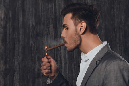 handome: Handome brutal man in suit on the grey background lighting a cigar Stock Photo
