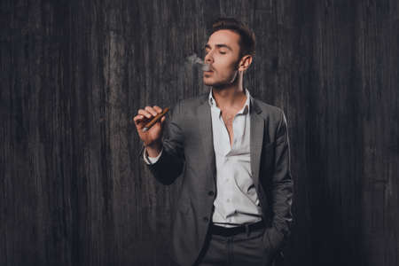 smoking a cigar: Handome brutal man in suit on the grey background smoking a cigar