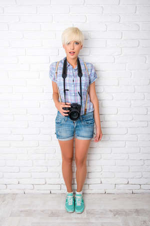 freelance: Funny beautiful girl is a freelance photographer with camera Stock Photo
