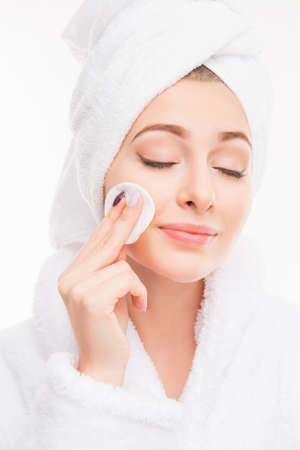 face close up: Pretty girl with towel on her head wash off makeup wiht closed eyes, close up photo Stock Photo