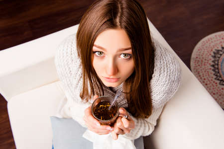 rheum: Top view photo of sick girl holding a cup of hot tea Stock Photo