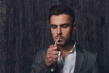 handome: Handome brutal man in suit on the grey background lighting a cigarette