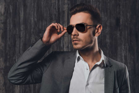 Handsome stylish man with glasses on the grey background