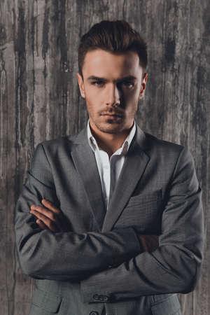 handome: Handome man in suit on the grey background crossing hands