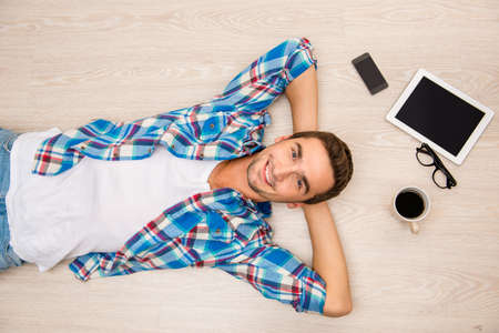 lunchtime: Handsome young man lying on wooden floor in his lunch-time