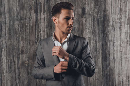 handome: Handome man in suit on the grey background fastening buttons on the sleeves