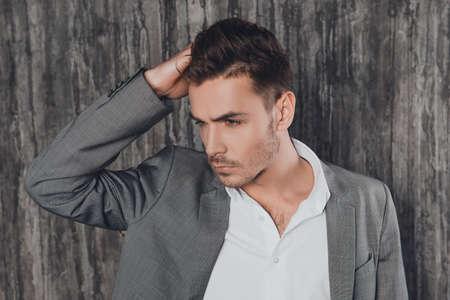 beau mec: Attractive man en costume sur le fond gris cheveux toucher Banque d'images